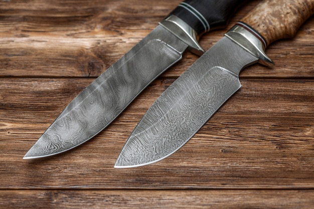 Hunting damascus steel knives handmade on wooden surface