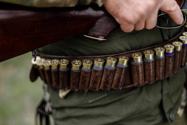 벨트에 사냥 장비 탄약 카트리지.