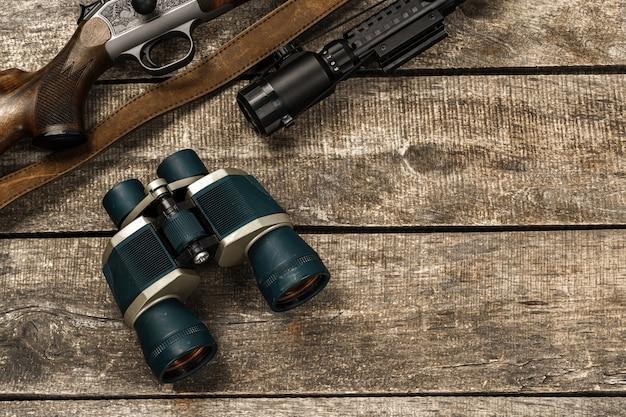 Бинокль охотничьего оборудования на деревянной поверхности крупным планом