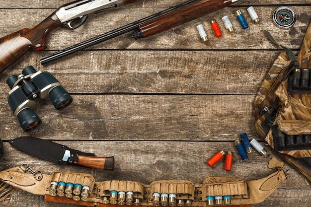 라이플 나이프 쌍안경 및 카트리지를 포함한 오래 된 나무 배경에 사냥 장비