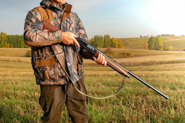 Охота. охотник в камуфляже с ружьем на охоте.