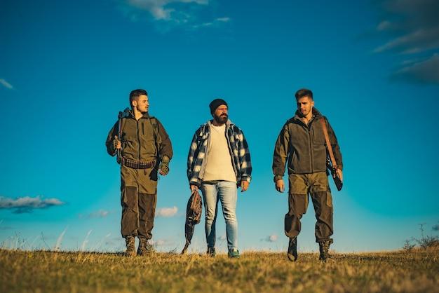 ロシアでの狩猟。狩りに散弾銃を持ったハンター。専門家のための狩猟用具。狩猟はハンターにとって残忍な男性的な趣味です。青い空の背景にツリーハンター。