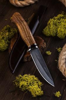 木製の背景にダマスカス鋼で作られたハンティングナイフ