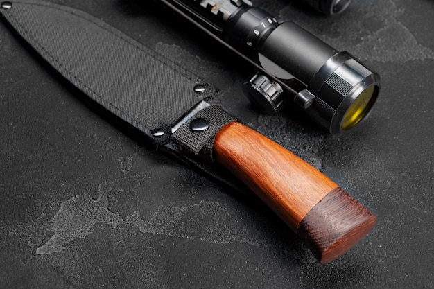 Hunting knife and optical sight for rifle on grey background