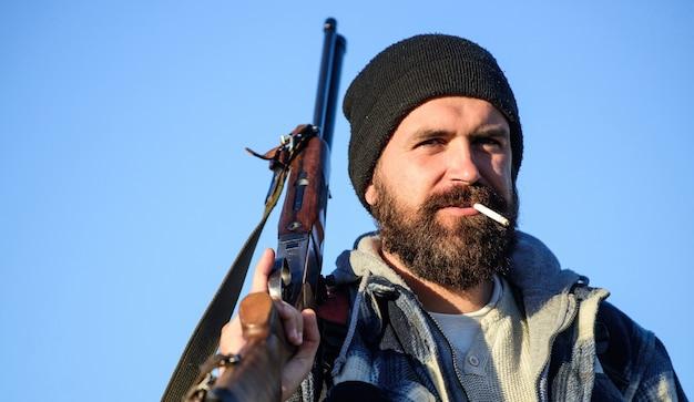Концепция мужского хобби охоты. человек жестокий бородатый парень егерь фон голубого неба. брутальность и мужественность. охотник с винтовкой крупным планом. парень бородатый охотник проводит досуг охотой и курением.