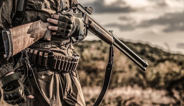 狩猟期間、秋の季節。銃を持った男性。バックパックと狩猟銃を持ったハンター。狩猟銃と狩猟フォームを持ったハンター。