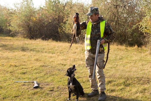 Период охоты, открыт осенний сезон. охотник с ружьем в руках в охотничьей одежде в осеннем лесу в поисках трофея. мужчина стоит с оружием и охотничьими собаками выслеживает дичь.
