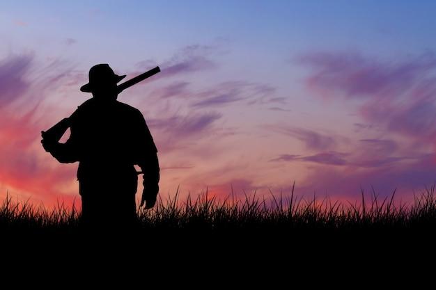 狩猟期間、秋のシーズンが始まります。トロフィーを求めて秋の森で狩猟服を手に銃を持ったハンター。男は武器と狩猟犬と一緒に立ってゲームを追跡します。
