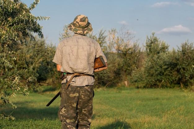 사냥 기간 가을 시즌 오픈 사냥복을 입고 손에 총을 든 사냥꾼