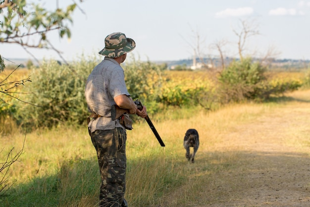 Hunting period autumn season open a hunter with a gun in his hands in hunting clothes