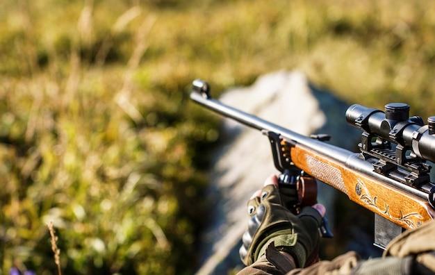 Период охоты. охотник целится. прицеливание стрелка в цель. мужчина на охоте. охотничье ружье. человек-охотник. мужчина с ружьем. закройте вверх. охотник с охотничьим ружьем и охотничьей формой для охоты.