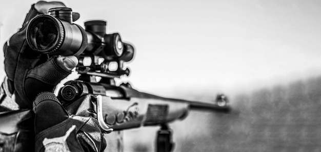 사냥 기간. 총을 든 남자. 확대. 사냥 총과 사냥을위한 사냥 형태를 가진 사냥꾼. 헌터가 조준하고 있습니다. 표적에서 사수 관찰입니다. 검정색과 흰색.