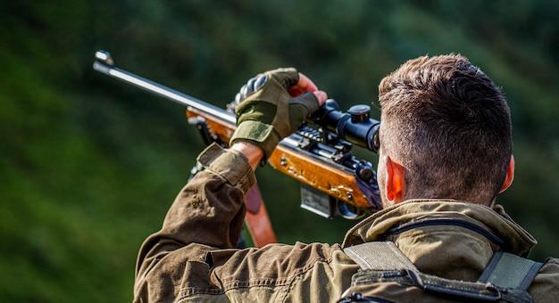 Период охоты. мужчина с ружьем. закройте вверх. охотник с охотничьим ружьем и охотничьей формой для охоты. охотник целится. мужчина на охоте. охотничье ружье. человек-охотник.