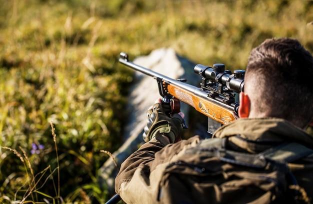 狩猟期間。銃を持つ男性。閉じる。ハンティングガンとハンティングフォームを持つハンター。