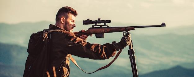 Период охоты. мужчина с ружьем. охотник с охотничьим ружьем и охотничьей формой для охоты. охотник целится. мужчина на охоте.
