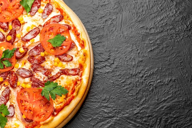 Hunting pizza on a black background, tomato-based with mozzarella