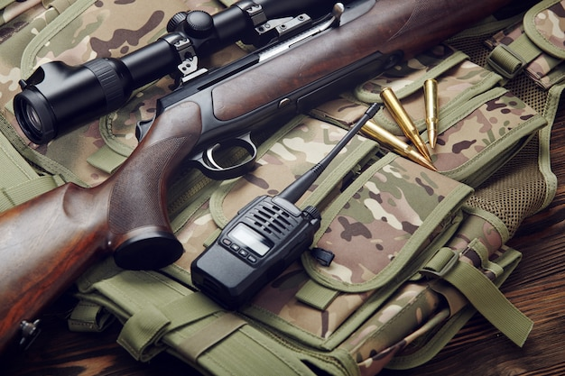 A hunting rifle, ammunition and a walkie-talkie lie on a camouflage vest on a table