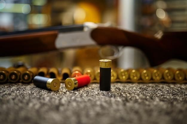 銃店のクローズアップのカウンターで狩猟用ライフル、装弾ベルト、カートリッジ、誰も。武器屋、弾薬の品揃え、銃器の選択、射撃の趣味とライフスタイル、護身術とセキュリティ