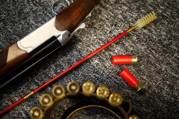 銃店のクローズアップのカウンターでライフル、装弾ベルト、槊杖を狩る、誰も。武器屋、弾薬の品揃え、銃の選択、射撃の趣味とライフスタイル、護身術とセキュリティ