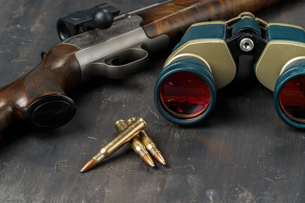 Hunting rifle and cartridges on dark wooden background