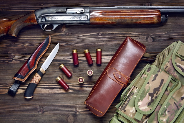 Hunting rifle, cartridges, knife on a wooden background
