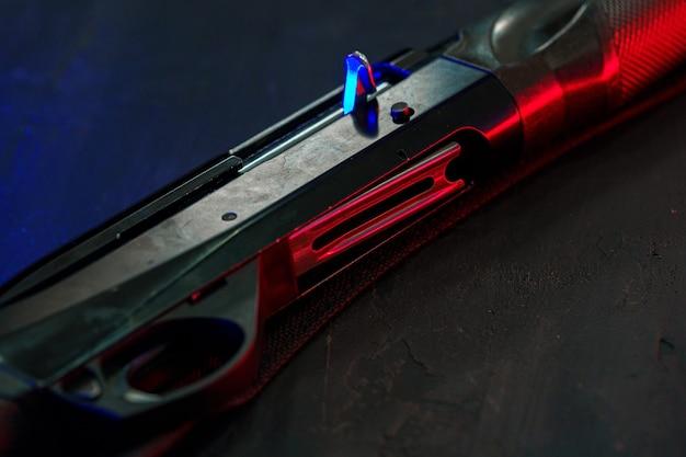 赤と青のバックライトと黒の背景にショットガンを狩る