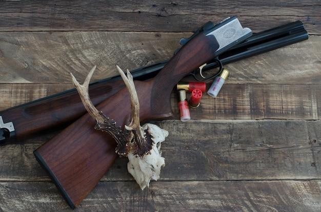 Охотничье ружье с патронами и оленьим черепом. вид сверху.