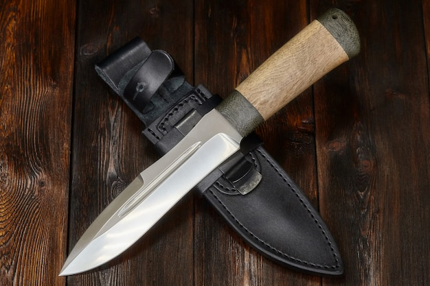Hunting steel knife handmade on a wooden surface, close-up