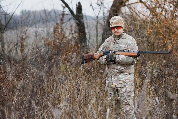 사냥, 전쟁, 군대 및 사람들 개념-숲에서 걷는 총을 가진 젊은 군인, 레인저 또는 사냥꾼
