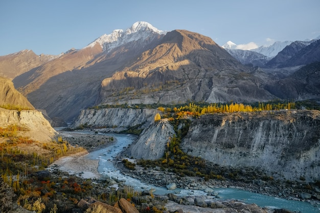 Hunza river flowing through karakoram mountain range against clear blue sky in autumn.