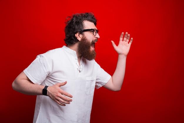 Торопливый бородатый мужчина в очках бежит по красному
