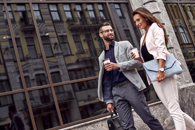 도시 거리에서 뜨거운 술을 마시며 걸어가는 두 명의 젊은 사업가를 만나기 위해 서둘러