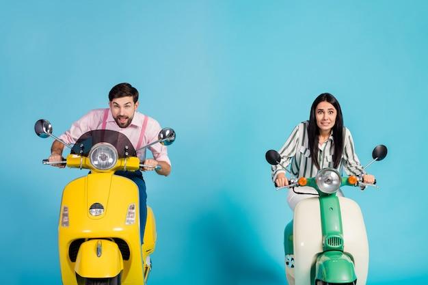서둘러! 서두르는 공항 여자 남자의 사진 두 복고풍 오토바이 큰 속도 다른 감정 중독 된 여행자 formalwear 옷 절연 파란색 벽