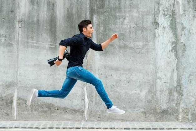 最初に急いで。コンクリートの壁に向かって走っている若い写真家の全長