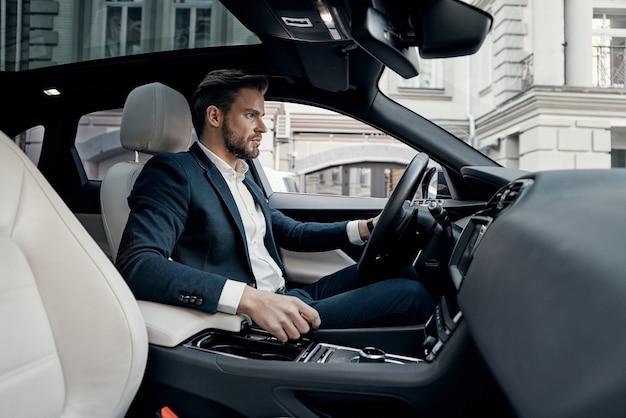 Спешите добиться цели. красивый молодой человек в полном костюме, глядя прямо за рулем автомобиля
