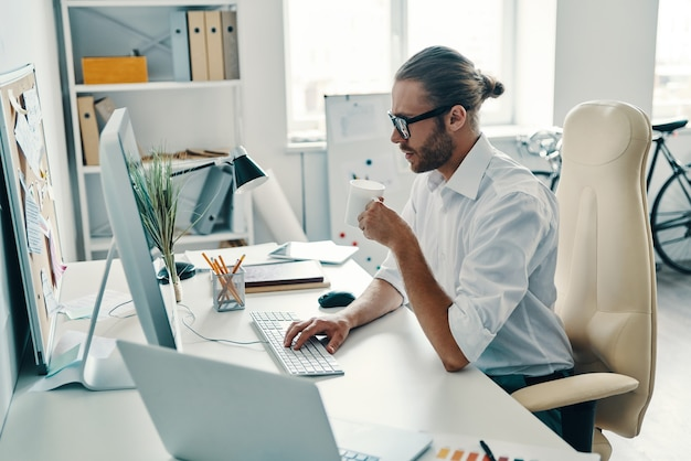 Спешите добиться цели. вдумчивый молодой человек в рубашке работает с компьютером и пьет кофе, сидя в офисе Premium Фотографии
