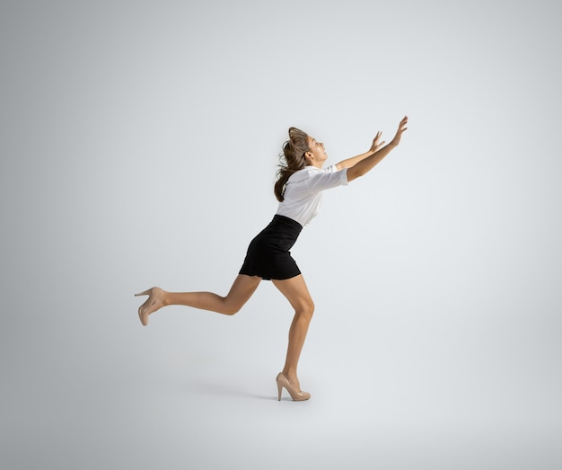 새로운 목표를 향해 서두르고 있습니다. 회색 벽에서 실행 사무실 옷에서 여자입니다. 모션, 작업에서 훈련하는 사업가. 스포츠, 새로운 활동에 대한 비정상적인 모습. 스포츠, 건강한 라이프 스타일.