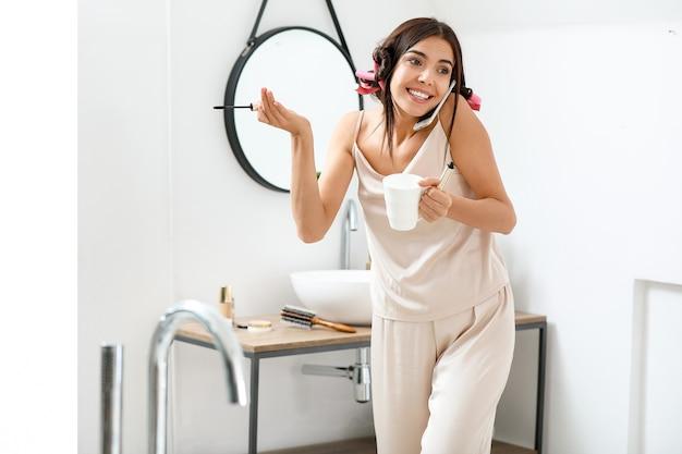電話で話し、朝のコーヒーを飲みながら化粧をする急いでいる女性