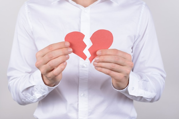 Hurt feelings marriage torn health care concept. cropped close up photo of exhausted with bad feelings crying husband showing two halves on one heart isolated grey background