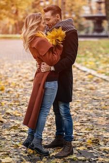Муж и жена обнялись, улыбаются, глядя друг на друга в осеннем парке