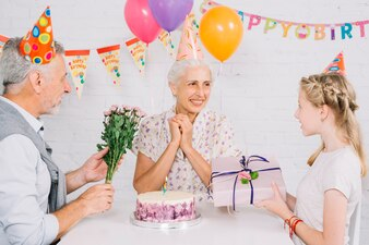 Husband and granddaughter giving birthday gift to happy woman with cake on desk