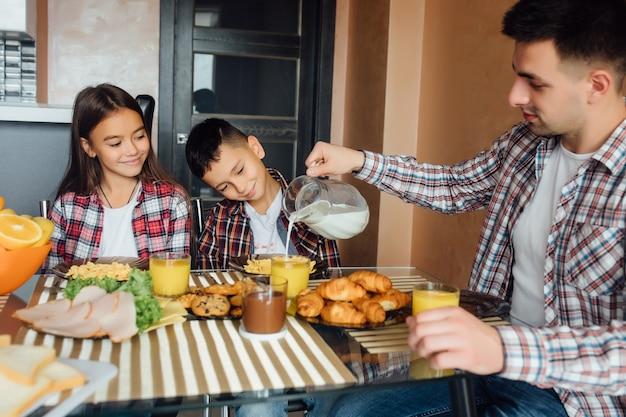 Муж и его маленький сын с дочерью сидят за кухонным столом и завтракают
