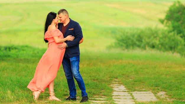 夫と妊娠中の妻が野原を歩いている