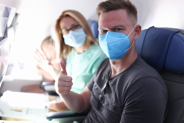夫と妻は医療用マスクを着て飛行機で飛んでいます。