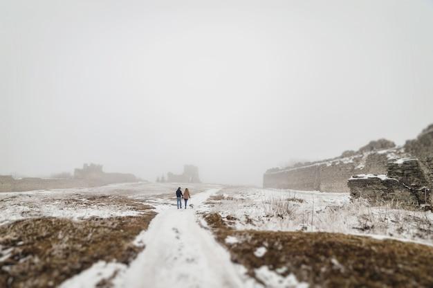 Зимой муж и жена идут по парку, держась за руки.