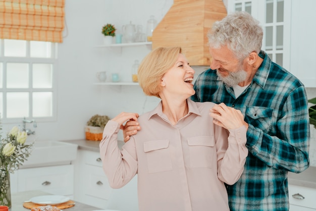 남편과 아내는 아침 식사 중에 집에서 포옹하고 있다