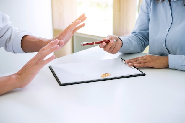 夫と妻は離婚協定を読んでおり、法令に署名するためのペンを提出しています