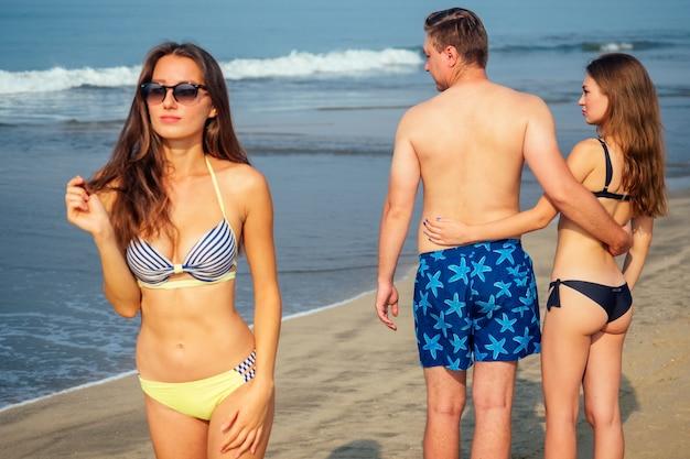 남편과 아내가 해변을 따라 걷고 있고 여자는 다른 사람의 아름다운 여자에게 남자를 질투합니다.