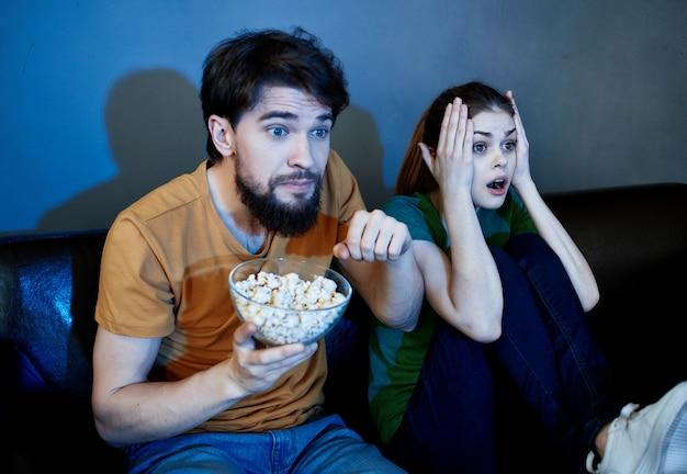 Муж и жена дома вечером на диване смотрят телевизор отдыхают попкорн