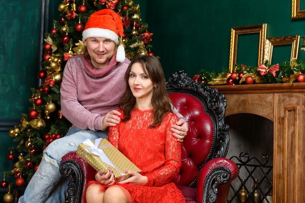 夫と妻は飾られたクリスマスツリーでクリスマスを祝う